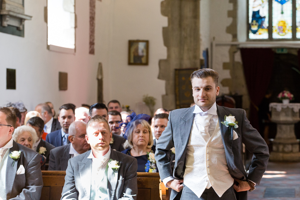 Groom stood at the top of the aisle waiting for his bride