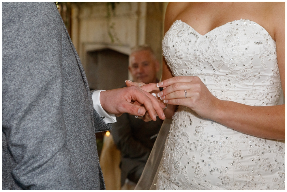 Bride puts ring on grooms finger
